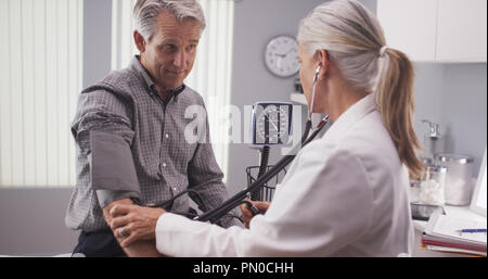 Professional doctor measuring senior man's blood pressure - Stock Photo