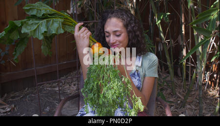 Young hispanic woman smelling and looking at vegetables. - Stock Photo