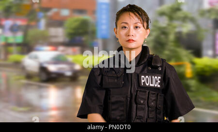 Asian American Woman Police Officer at Crime scene looking Serious - Stock Photo