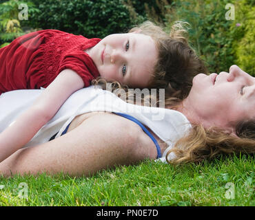 A young girl resting with her mother in the grass - Stock Photo
