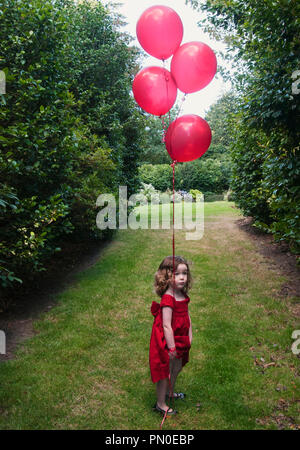 A girl in a red dress holding a red balloon.