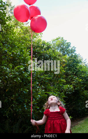 A young girl in a red dress holding balloons.