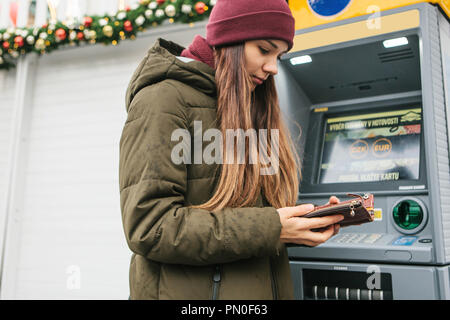 A young woman tourist or girl takes money from an ATM in Prague in the Czech Republic during the Christmas holidays for further tourism around the city. - Stock Photo