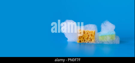 White soap bubbles foam and yellow green cleaning sponges on blue background. Suds shower texture macro view photo, shallow depth of field. Copy space. - Stock Photo