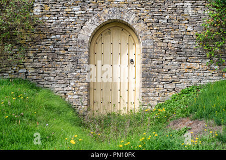 Arched wooden Garden door and cotswold stone wall in front of a house in the cotswold village of Calmsden, Cotswolds, Gloucestershire, England - Stock Photo