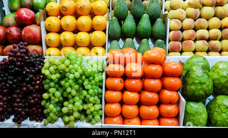 Assortment of fresh fruits and vegetables on market counter in a wooden boxes