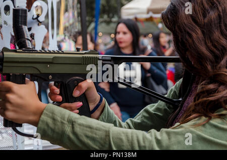 Little girl playing with a paintball gun shooting to the target - Stock Photo