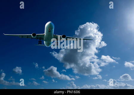 An artistic skyscape view of a commercial passenger jet aircraft flying in a vibrant blue sky, with bright white coloured billowing Cumulonimbus clouds - Stock Photo