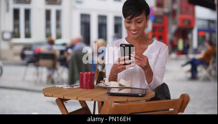 Pretty black woman at cafe in Bruges video chats with a friend on smartphone - Stock Photo
