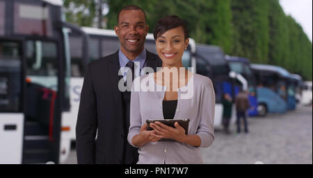 Two young African tour guides posing proudly near some tour buses - Stock Photo