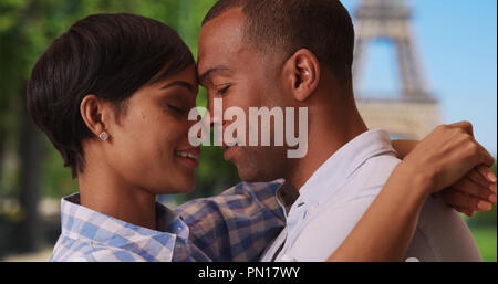 Ethnic couple in love get intimate near Eiffel Tower in Paris - Stock Photo