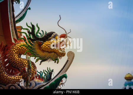 Beautiful statue of Chinese dragon on a roof top in Chinese temple under blue sky background. - Stock Photo