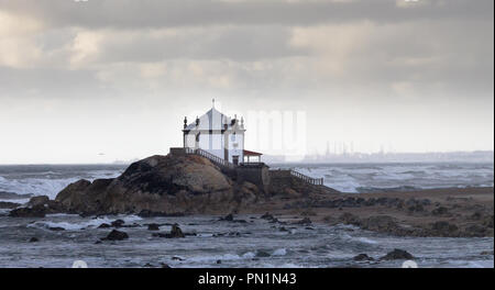 At the beach, a chapel sits on top of the rocks, during a stormy day. - Stock Photo