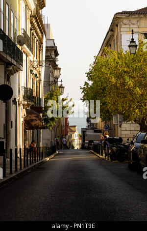 A tight street in Lisbon with no cars passing by. - Stock Photo