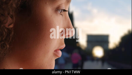 Close up of sad young woman staring at the ground outside grief stricken - Stock Photo