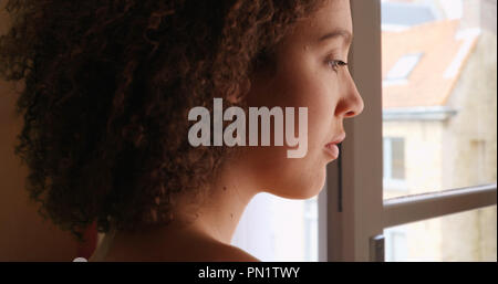 African American female stares outside her window looking sad - Stock Photo