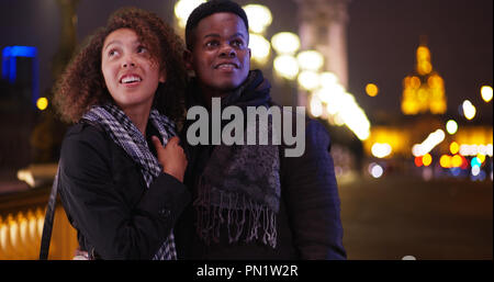 Happy African American couple on Pont Alexandre III bridge at night - Stock Photo