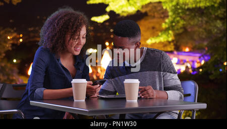 Black male and female meeting for coffee at night use tablet computer