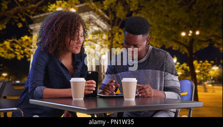 Smiling black male and female meeting for coffee at night use tablet