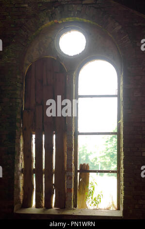 broken window of an old building, old red brick building, Church in the village of Zapovednoye (Seckenburg), Kaliningrad region, Russia - Stock Photo