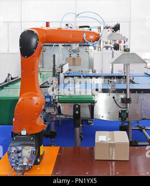 Articulated robotic arm at packaging line in factory - Stock Photo