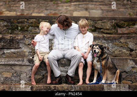 A young, loving father is sitting outside on stone steps, with his two boy children and their adopted pet German Shepherd dog on a Summer day. - Stock Photo