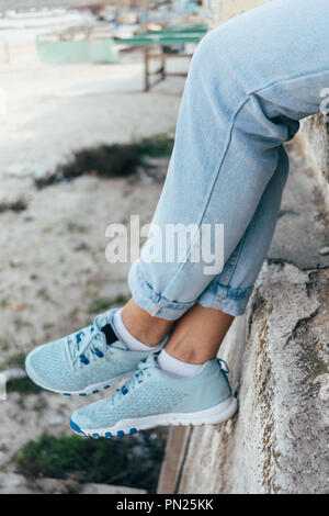 Close-up of female legs in blue rolled up jeans and sneakers. Young woman sitting on high concrete parapet in the city, vertical framing. - Stock Photo