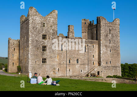 People sit & have picnic under blue sky by historic medieval castle in beautiful countryside - Bolton Castle, Wensleydale, North Yorkshire England, UK - Stock Photo