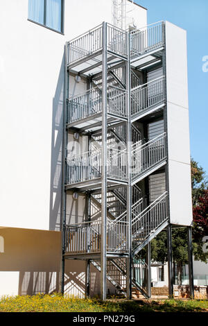 Fire Exit. Metal fire escape outside ladder on modern apartment building for emergency. Fire stairs on the building. A staircase on the external wall - Stock Photo