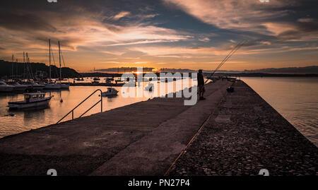 Fisherman at sunset on Brixham breakwater - Stock Photo