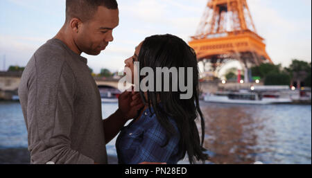 Passionate black male and female show love for each other near Eiffel Tower - Stock Photo