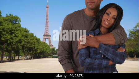 Pretty African female standing near Eiffel Tower joined by loving boyfriend - Stock Photo