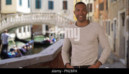 Confident African male stands proudly while traveling in Venice Italy - Stock Photo