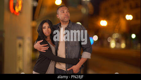 Black couple walking together along city street together at night - Stock Photo