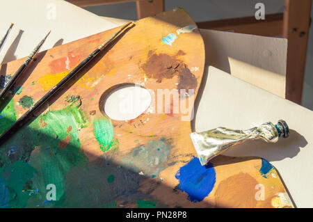 Materials to paint: blank canvas, palette full of colorful paint, brushes and oil paint tube with sunbeams entering through a window. - Stock Photo