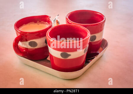 Anyone for coffee, three red french coffee cups ready to be drunk - Stock Photo