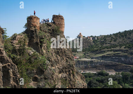 Tourists at the top of the Narikala Fortress in Tbilisi, Georgia. To the right is the Botianical Gardens. - Stock Photo