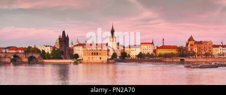 Prague, panoramic image of the riverside on sunset. Charles Bridge, Novotnevo Lavka and historic buildings of the city center are bathing in warm even - Stock Photo