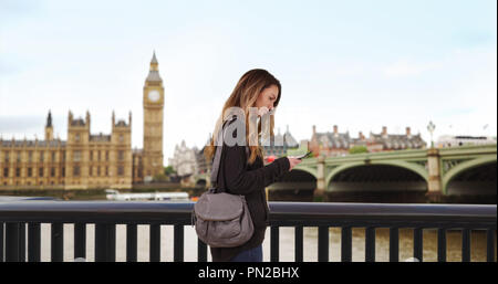 Caucasian woman lost in London uses smartphone for directions - Stock Photo