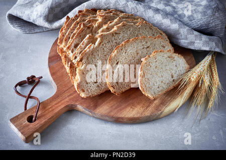 Slliced white round bread with wheat ears on wooden cutting board on gray stone background - Stock Photo