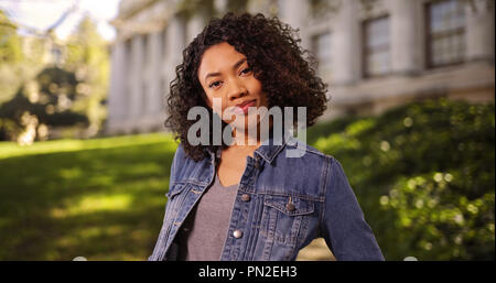Independent young African-American woman posing confidently on college campus - Stock Photo