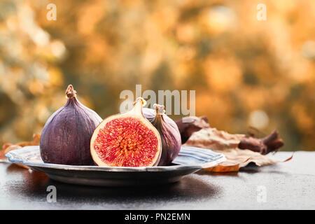 Closeup on fresh figs on dark shiny stone plate outdoors, toned image - Stock Photo