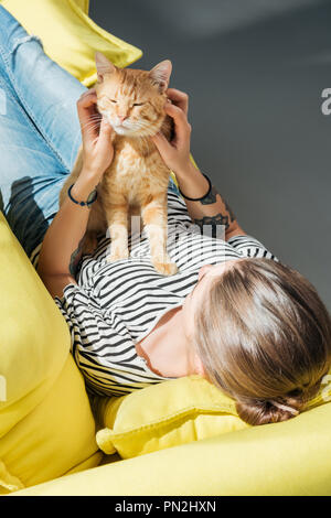 high angle view of girl playing with cute red cat while lying on yellow couch - Stock Photo