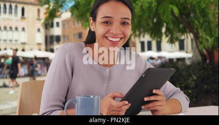Happy Hispanic female uses tablet outside at Venice cafe - Stock Photo