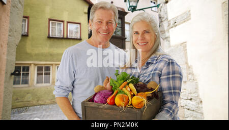 Beautiful white senior couple carrying hand picked vegetables - Stock Photo