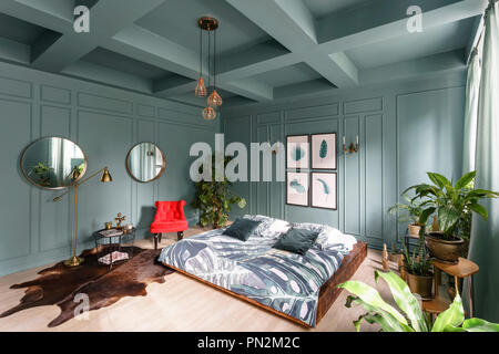 Morning interior in bedroom hotel. Bright and clean interior design of a modern room with bed, chair and houseplant. Mirrors on walls - Stock Photo