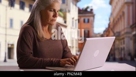 Old Caucasian lady browses web on laptop in public setting in Rome - Stock Photo