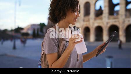 Smiling black female uses tablet near Roman colosseum holding water bottle - Stock Photo