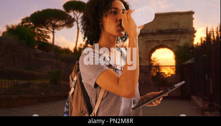 Attractive black female tourist uses tablet outdoors in Rome at golden hour - Stock Photo