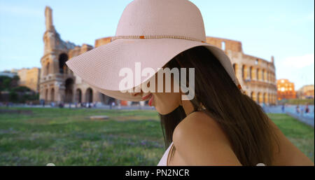 Close up of attractive Latina tourist standing near Roman colosseum smiling - Stock Photo
